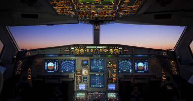 Purple sunset from a commercial airliner's cockpit. The many brightly coloured screens, switches and buttons stand out clearly against the dark background of the flightdeck. All markings that could make this aircraft identifiable have been removed.